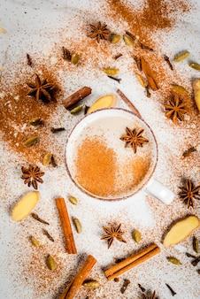 De traditionele indische thee van masalachai met kruiden - kaneel, witte kardemom, anijsplant,. bovenaanzicht copyspace