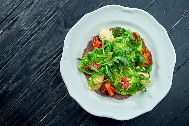 De traditionele italiaanse aperitiefsalade is vitello tonnato. dungesneden rundvlees met rucola, tomaten en pesto, geserveerd in een wit bord op een donkere ondergrond