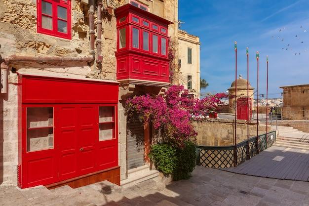 De traditionele maltese straat met rode telefooncel en gebouw met kleurrijke luiken en balkons bij zonsopgang, valletta, hoofdstad van malta