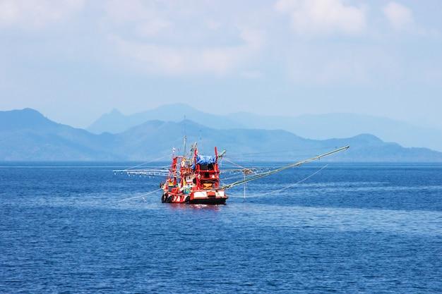 De traditionele oranje thaise vissersboot die in de baai van thailand dichtbij koh drijven chang op dag de heldere hemel.