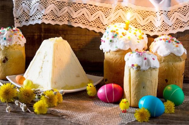De traditionele pasen behandelt taarten en kleurrijke paaseieren op een tafel in een rustieke stijl.