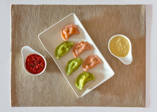 De traditionele russische en oekraïense bollen van voedselvareniki met mosterd en tomatensaus op een witte plaat.