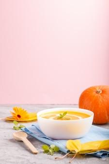 De traditionele soep van de pompoenroom met in witte kom op een grijze en roze achtergrond