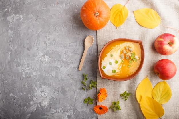 De traditionele soep van de pompoenroom met zaden in kleikom op een grijze concrete achtergrond. bovenaanzicht