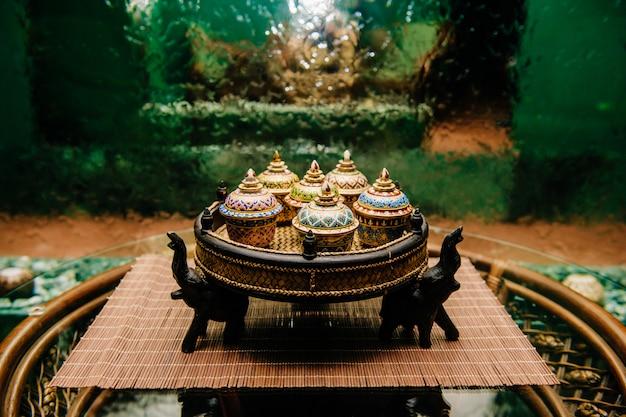 De traditionele thaise beroemde theeketel van het ceremoniebrons op rieten presenteerblad met lotusbloembloemen, kop, suiker en koekjes op rotanlijst met glazige oppervlakte met abstracte watervalmuur op achtergrond.