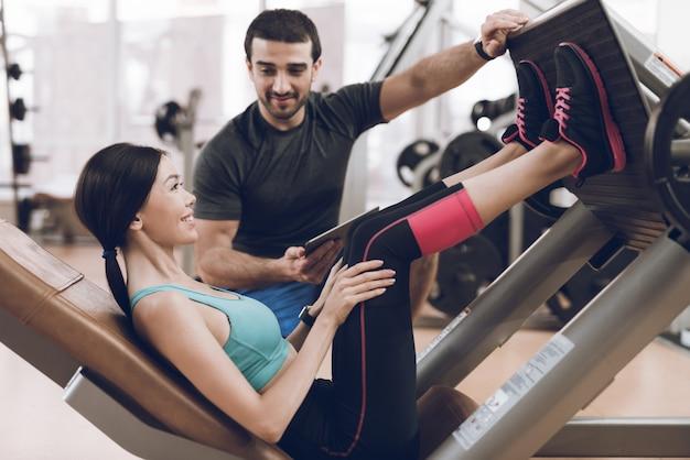 De trainer laat het meisje zien hoe ze haar benen moet slingeren
