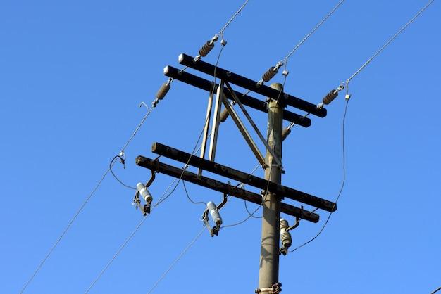 De transmissiepool van de elektriciteit onder blauwe hemel