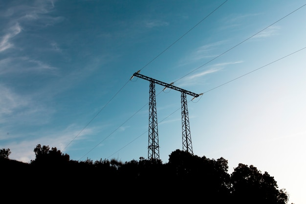 De transmissiepyloon van de elektriciteit die tegen blauwe hemel wordt gesilhouetteerd