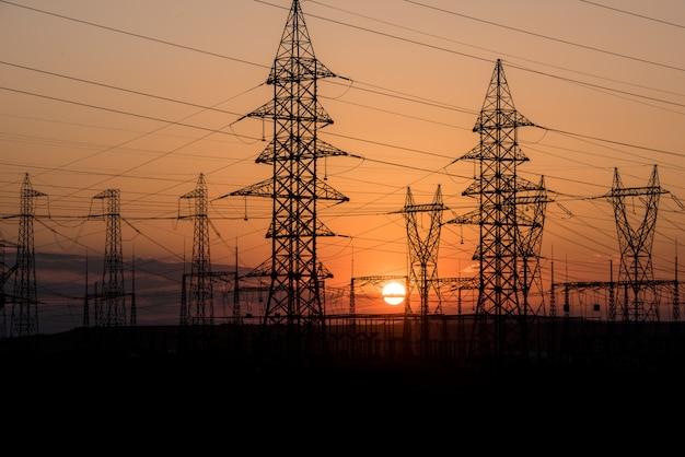 De transmissiepyloon van de elektriciteit die tegen zonsonderganghemel wordt gesilhouetteerd. elektriciteit achtergrond.