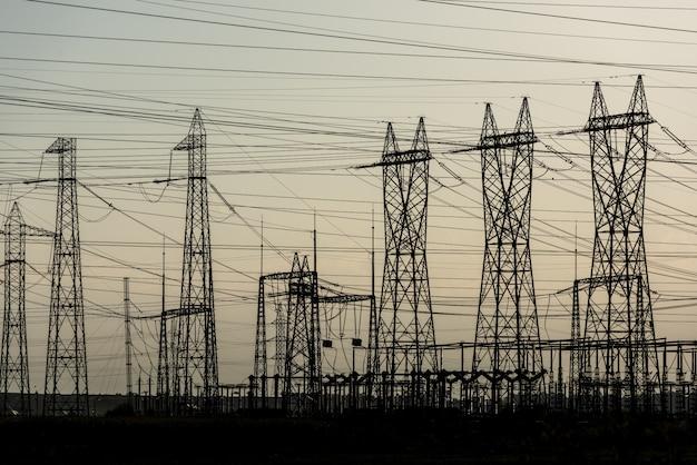 De transmissiepyloon van de elektriciteit die tegen zonsonderganghemel wordt gesilhouetteerd. hoogspanning elektrische toren