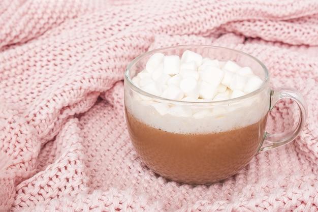De transparante kop van cacao met heemst en giftdoos met boog op roze gebreide plaid, sluit omhoog. winter gezellig concept
