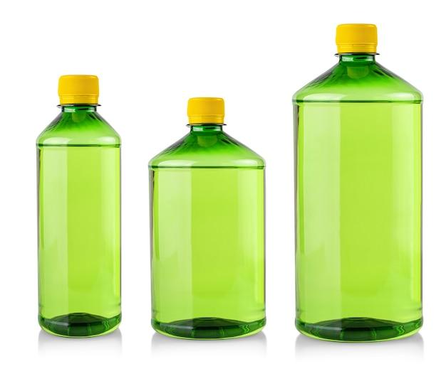 De transparante plastic flessen met groene chemische vloeistof met etiket op wit