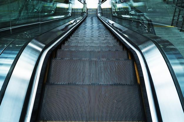 De trappen van de roltrap dalen af in de wachtkamers van het station. de trap oplopen. elektrische roltrap. selectieve focus