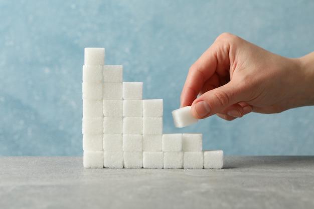 De treden van suiker en vrouwelijke hand met suikerkubus, sluiten omhoog