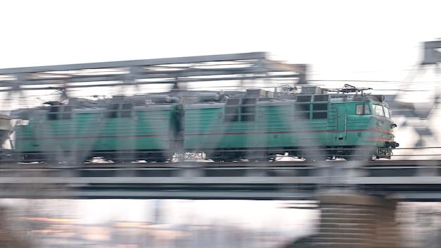 De trein rijdt met hoge snelheid over de spoorbrug. zware industrie, vracht.