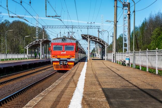 De trein van de russische spoorwegen vertrekt vanaf het perron bij het provinciale station op een heldere zonnige dag.