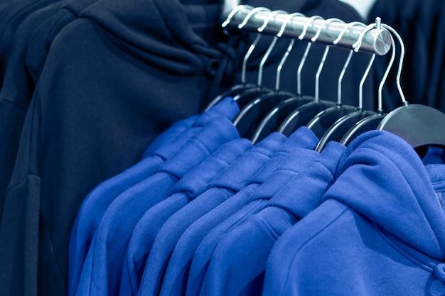 De trendkleur van het jaar 2020 classic blue. hoodies op hangers in een kledingwinkel, close-up.