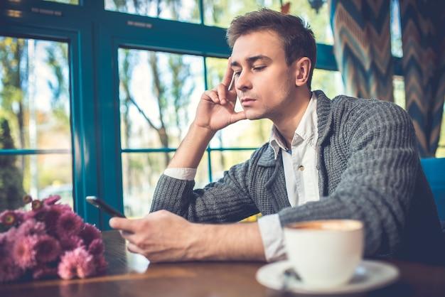 De trieste man met een telefoon zit in het restaurant