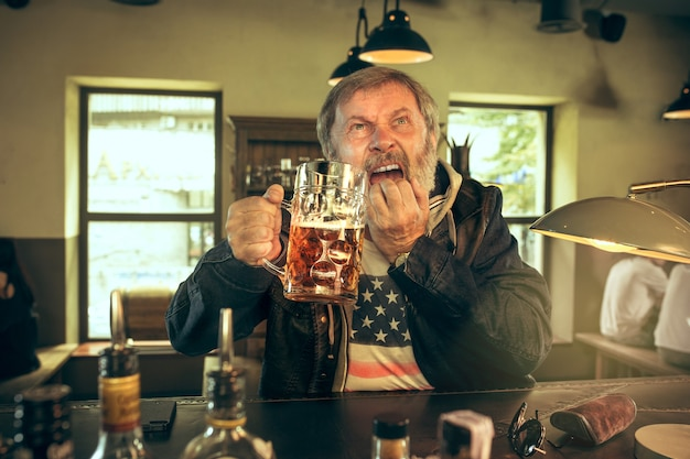 De trieste senior bebaarde man bier drinken in de pub