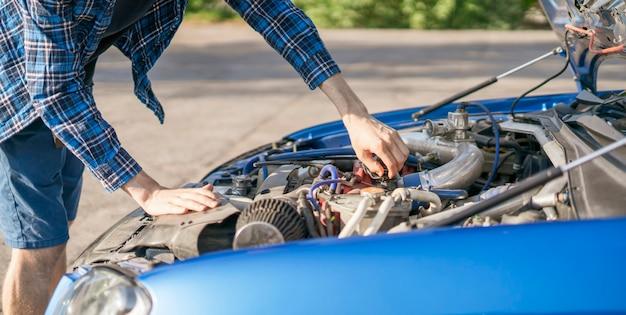De trieste teleurgestelde man die met geopende motorkap naast de auto staat, lost wat motorproblemen op