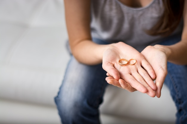 De trieste vrouw kijkt naar de ring in de palm voor hem, nostalgisch over een voormalige echtgenoot, familie, huwelijk. het concept van een relatie, echtscheiding.