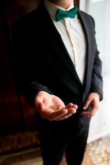 De trouwringen van de bruidegomholding op de palm