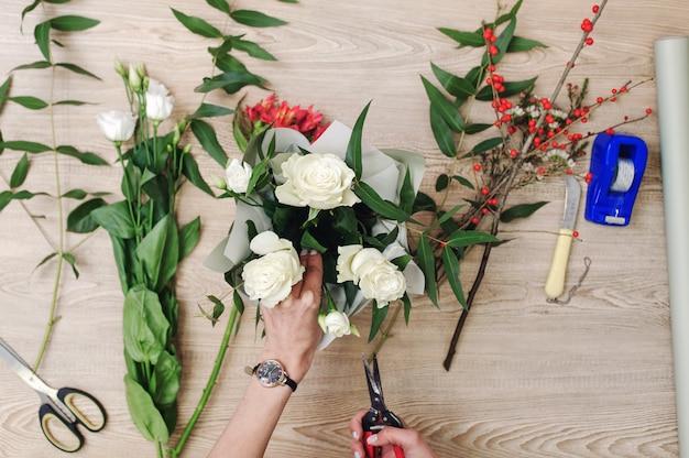 De tuinman in de bloemenwinkel maakt boeket. lifestyle bloemenwinkel. mooie bloemsamenstelling. detail.