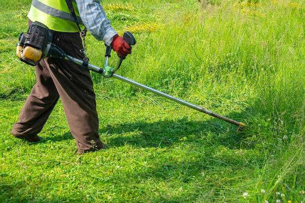 De tuinman maait gras door grasmaaier