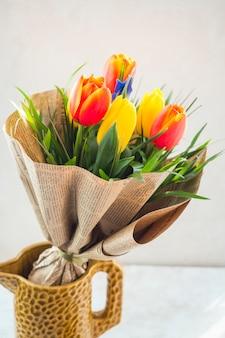 De tulp bloeit boeket in pakpapier in kruik