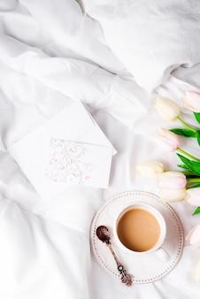 De tulpen bloeien met kop van koffie en prentbriefkaarvlak leggen ochtend in bed