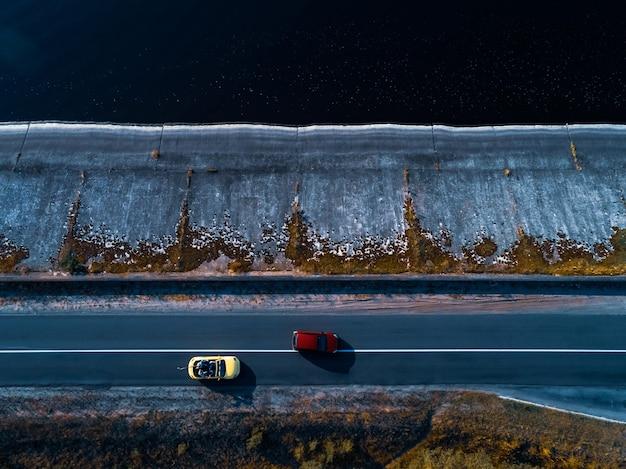 De twee auto's rijden op de kustweg