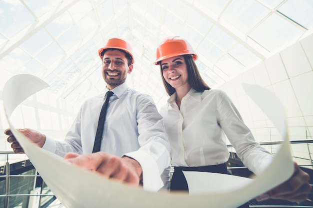 De twee bouwers in een helm houden het projectplan in het gebouw