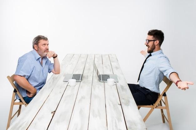 De twee collega's die op kantoor aan witte achtergrond samenwerken