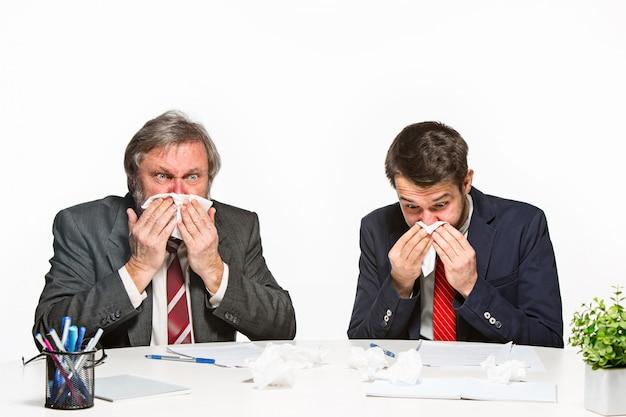 De twee collega's die op kantoor aan witte achtergrond samenwerken.