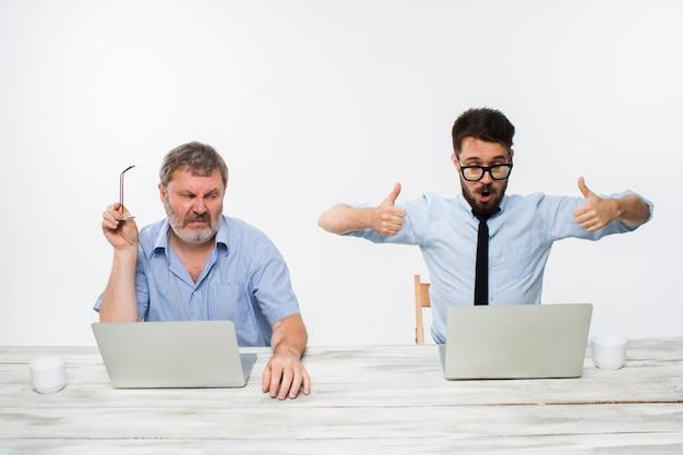 De twee collega's die op kantoor aan witte muur samenwerken