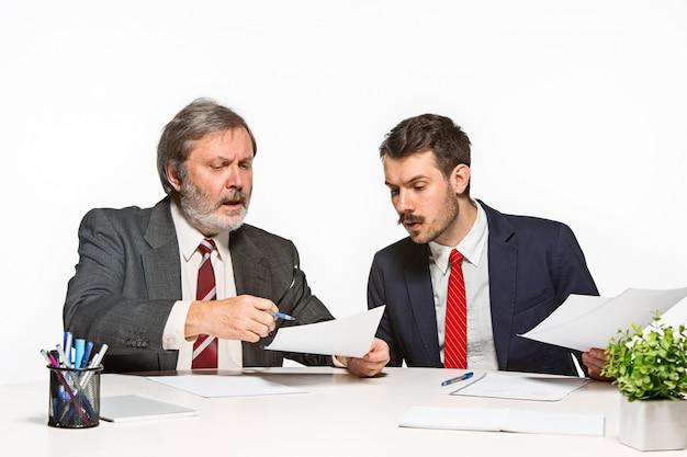 De twee collega's die op kantoor aan witte studio samenwerken