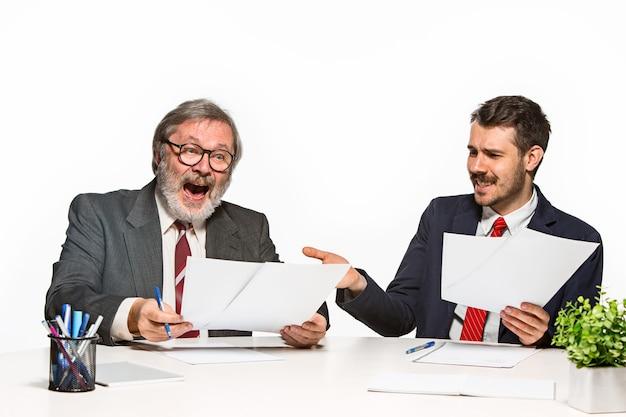 De twee collega's die op kantoor op witte achtergrond samenwerken. ze bespreken actief en emotioneel de huidige plannen