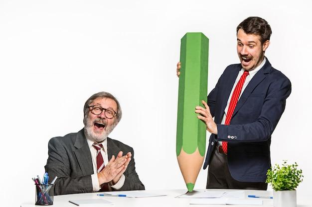 De twee collega's werken op kantoor samen met een enorm gigantisch potlood