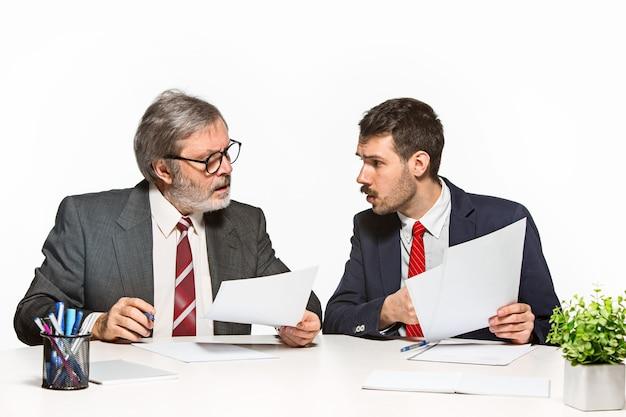 De twee collega's werken samen op kantoor op wit.