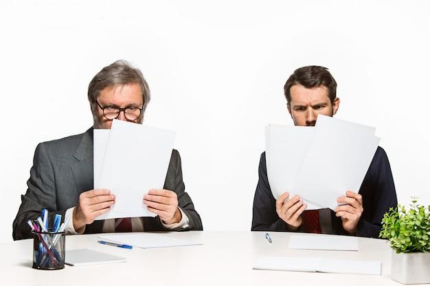 De twee collega's werken samen op kantoor.