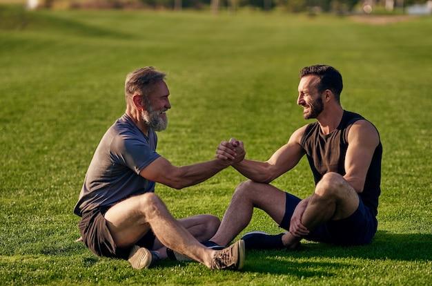 De twee gelukkige mannen die op het gras zitten en groeten