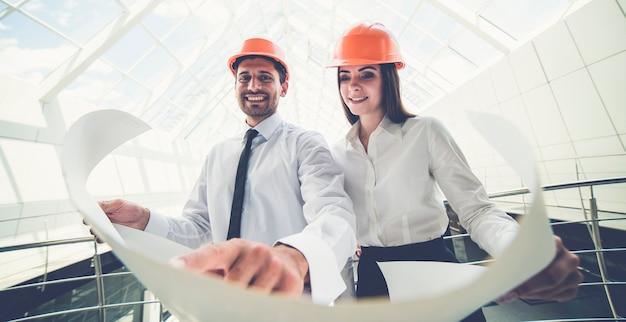 De twee glimlachbouwers in een helm houden het projectplan in het gebouw