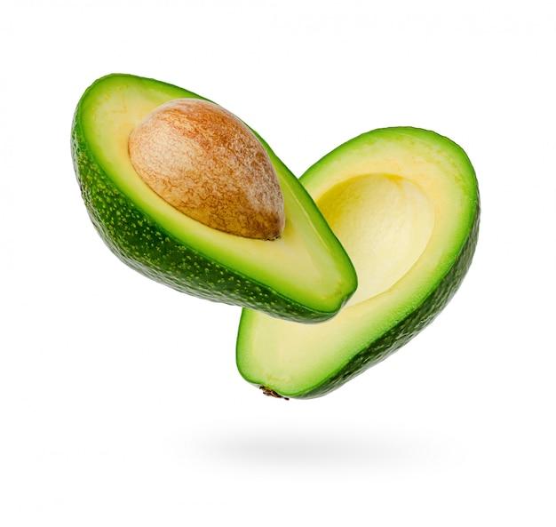 De twee helften van verse die avocado op wit worden geïsoleerd