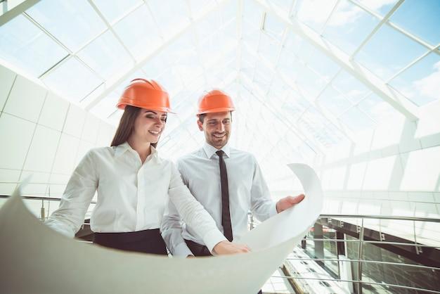 De twee ingenieurs houden het projectplan in het gebouw