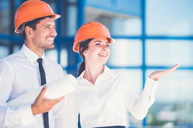 De twee ingenieurs met een papieren gebaar op de achtergrond van het gebouw