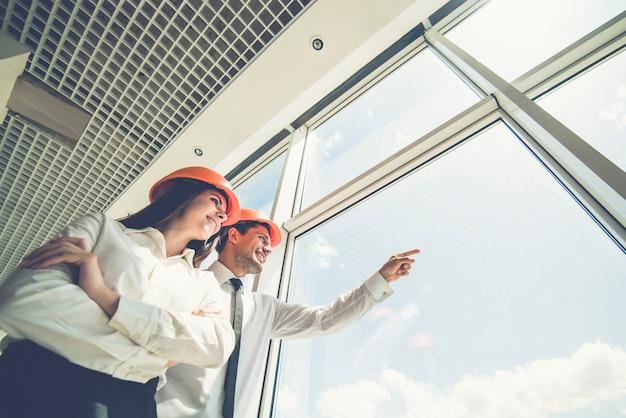 De twee ingenieurs staan bij het raam en gebaren