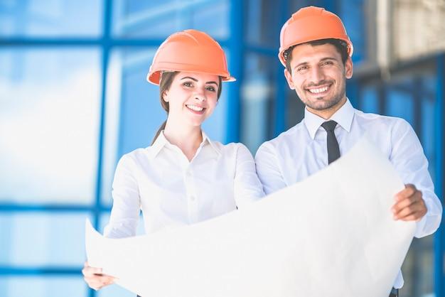 De twee ingenieurs staan met een papier op de achtergrond van het gebouw