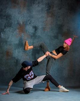 De twee jonge meisje en jongen dansen hiphop in de studio