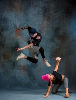 De twee jonge meisje en jongen dansen hiphop