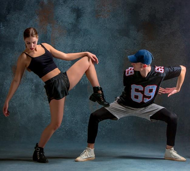 De twee jonge meisje en jongen hip hop dansen op de blauwe